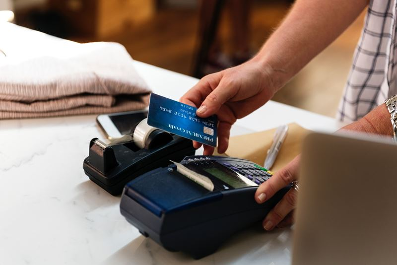 Man holding a debit card and working a credit card processing machine